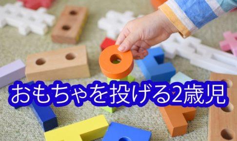 おもちゃを投げる2歳児